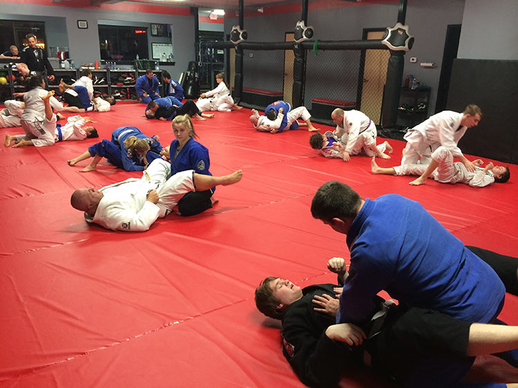 Photo of a Brazilian Jiu-Jitsu fundamentals class, where the students are performing basic drills.
