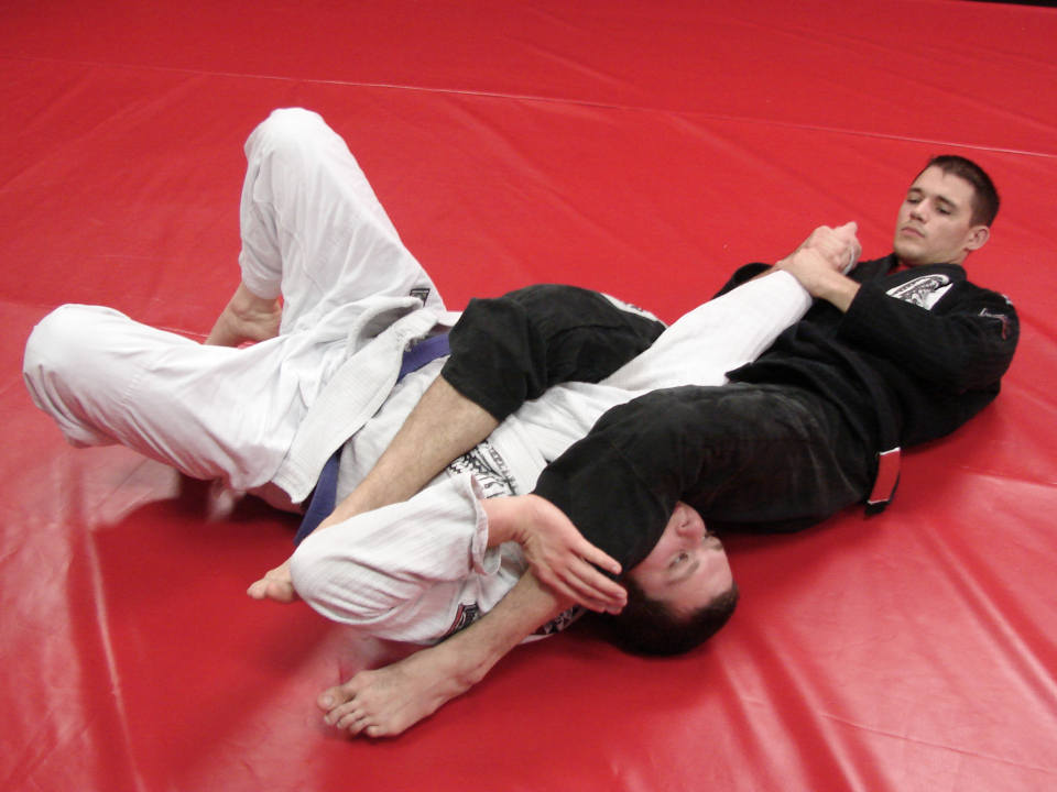 Photo of Coach James Clingerman demonstrating a Brazilian Jiu-Jitsu armbar