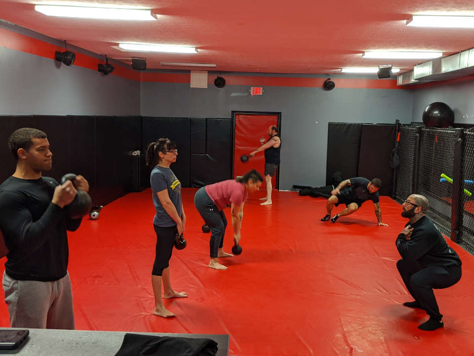 Photo of people working out with kettlebells in the Combat Conditioning class at Indiana Brazilian Jiu-Jitsu Academy
